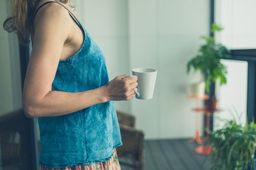Woman on balcony with cup of coffee