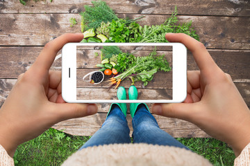Woman taking picture of vegetables