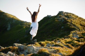 Young woman in white dress running in the mountains. Woman jumping on mountain peak rock. Beautiful girl looking happy and smiling