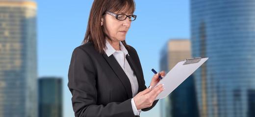 Mature businesswoman taking notes
