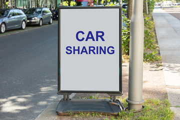 Car sharing sign on board by street