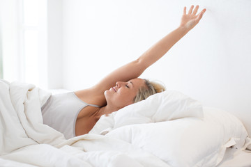 Happy young woman stretching in bed after sleep