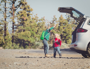 family car travel - happy little boy and girl get ready for hiking