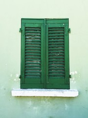 Wooden green window of a green house (Pesaro, Italy)