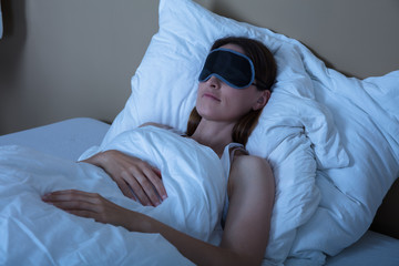 Woman Sleeping In Bed With Eye Mask