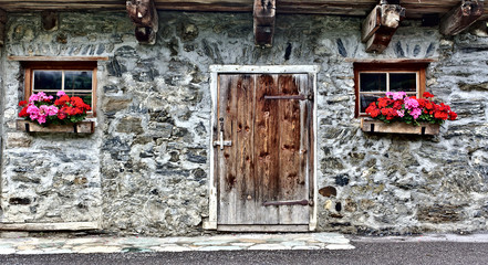 Old farm house made of field stones with wooden door, two windows and red flowers