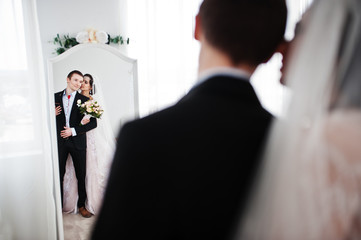 Gorgeous wedding couple enjoying each other's company in front of a mirror.