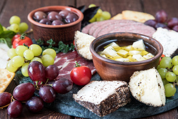 Cheese and meat appetizer selection. Variety of cheese, salami, prosciutto, bread, baguette, grapes, olives