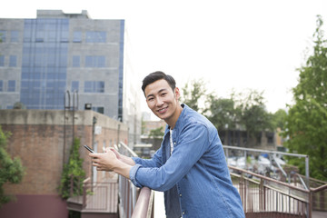 Cheerful young man holding a smart phone