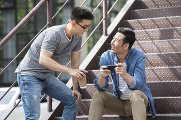 Young men having coffee break outdoors