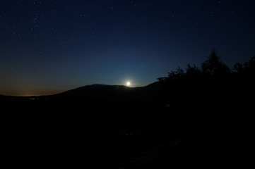 A moon rising from behind a mountain. Dark sky and bright spot from moonlight.