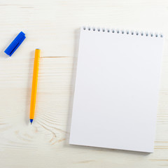 school empty notebook and pen, frame for your text, light wooden background, top view. Concept of back to school or education