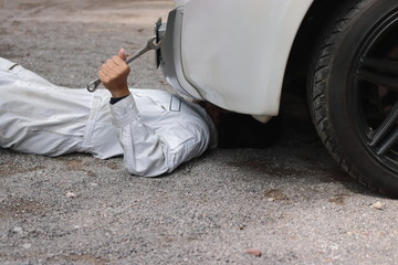 Side view of mechanic in white uniform lying down and fixing under car. Auto repair service.