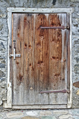 Old wooden door with grey field stone wall