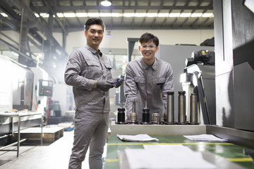 Confident engineers working in the factory