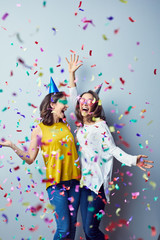 Couple of gorgeous laughng young women raising arms and cheering with birthday hats and accessories with confetti
