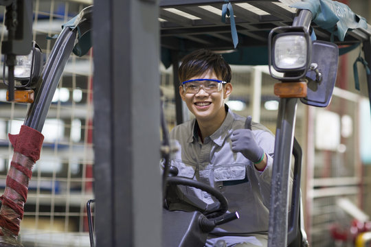 Young workman driving forklift in the factory