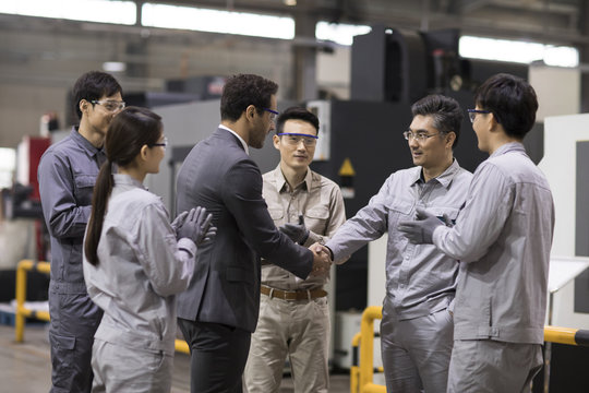 Businessman and engineer shaking hands in the factory