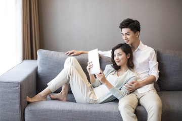 Cheerful young couple using digital tablet at home