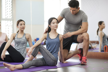 Young women working with trainer at gym