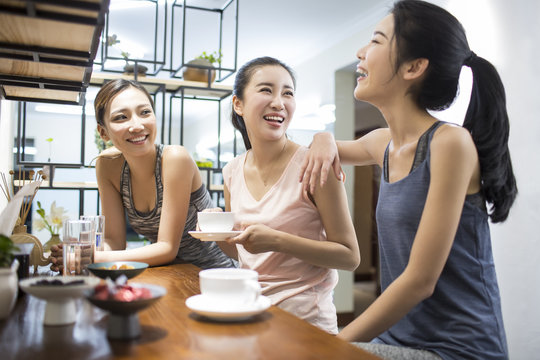 Smiling women sitting together and having coffee