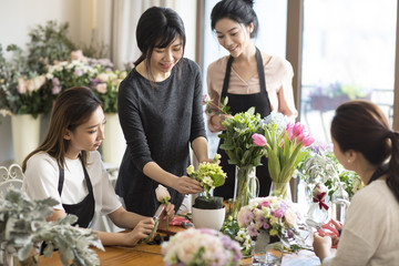 Young women learning flower arrangement