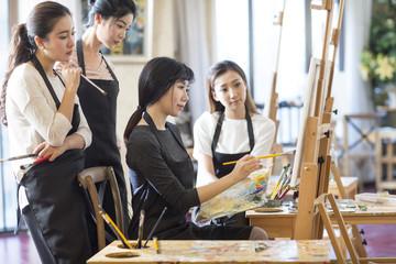 Art teacher with young women in studio