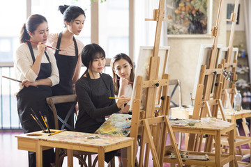 Art teacher with young women in studio