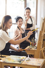 Young women painting in studio