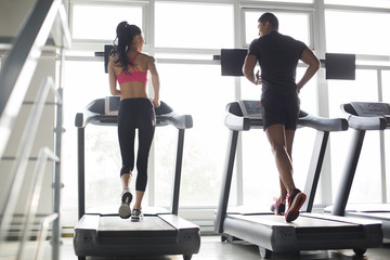 Rear view of couple exercising on treadmills in gym