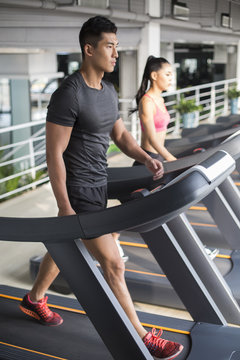Young man exercising on treadmill in gym