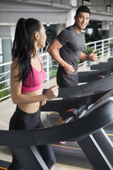 Young couple running on treadmills in gym