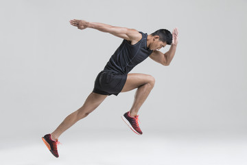 Male athlete running against white background