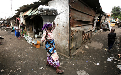 A woman is seen with kitchen tools made of recycled sheet metal in a recycling area in Anoumambo, Abidjan