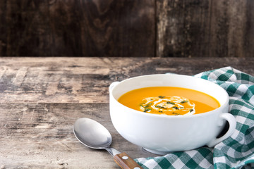 Pumpkin soup in white bowl on wooden table