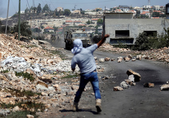 Palestinian protester hurls stones at Israeli troops during clashes in the West Bank village of Kofr Qadom near Nablus
