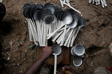 A man works on kitchen skimmers made of recycled sheet metal at his recycling warehouse  in Anoumambo, Abidjan