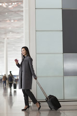 Businesswoman with wheeled luggage in airport lobby