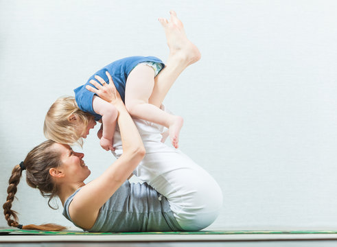 Mom and child are practicing yoga at home