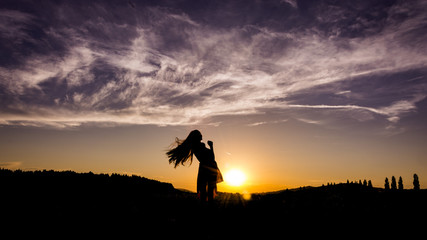 The silhouette of girl before the sun during sunset. The girl´s hair is ruffled in the air.