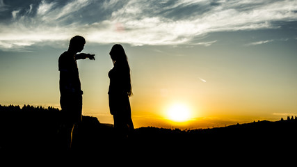 The silhouette of couple. The boy is showing something to the girl.  Maybe, they argue among themselves.