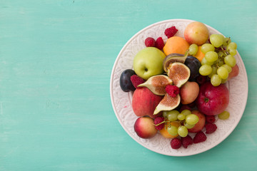 Top view on assortment of juicy fruits on white plate and turquoise wooden table background. Organic raspberries, apricots, apples, figs,plums, grapes - summer dessert or snack. healthy eating concept