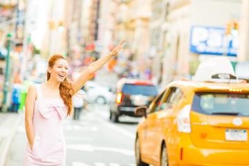 A young woman hailing a yellow taxi while walking on a street in New York city