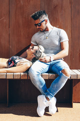 Portrait of handsome couple in casual clothing with sunglasses sitting on wood bench, joyful smiling expressions with heads together. Concept Loving Couple.