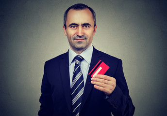 Happy mature business man offering new credit card