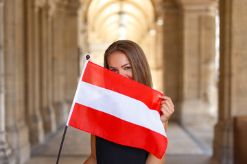 Happy young woman covering her face with austrian flag