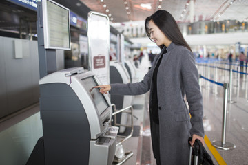 Businesswoman using ticket machine at the airport
