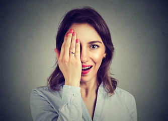 Young surprised woman hiding half face with her hand