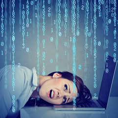 Desperate stressed woman resting head on laptop with binary code falling down