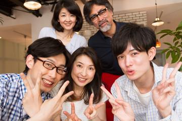 笑顔で全員の記念写真を撮影している家族